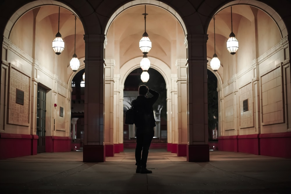 man in black jacket standing on hallway