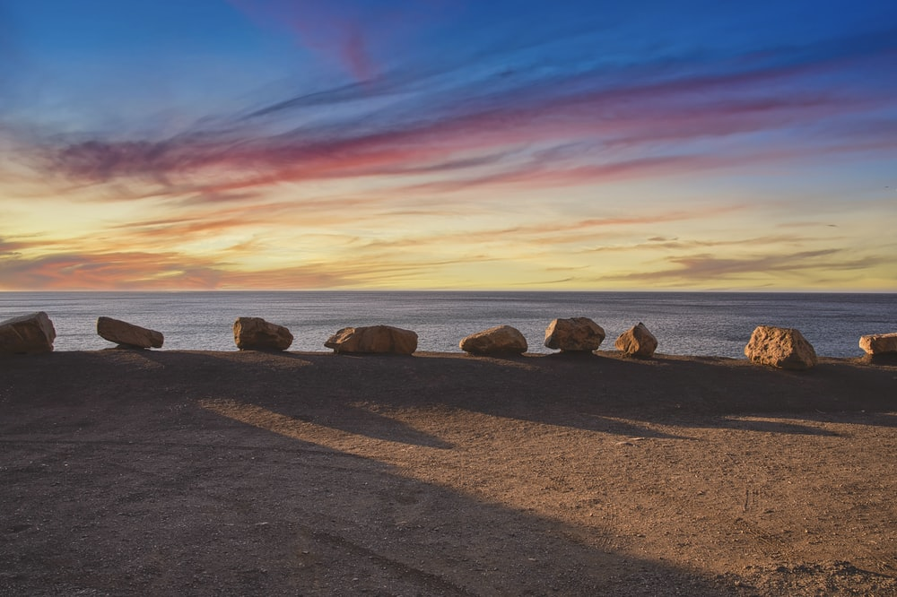 brown rocks on brown sand near body of water during sunset