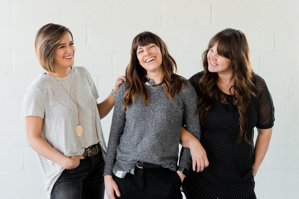 3 women smiling and standing beside white wall