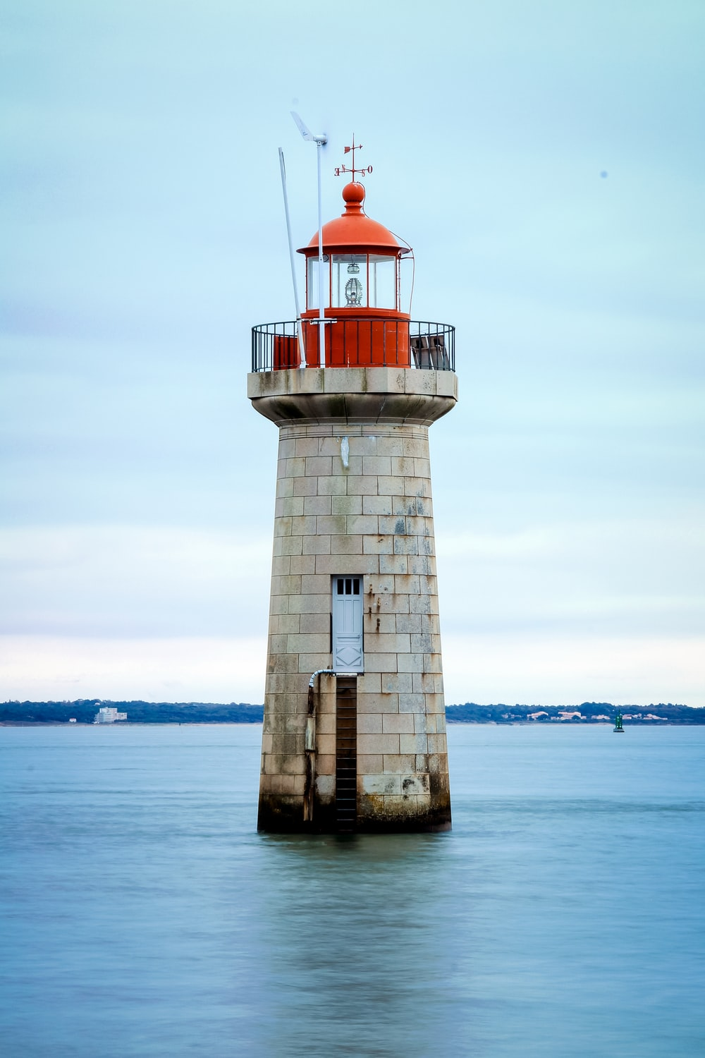 white and red lighthouse on body of water during daytime