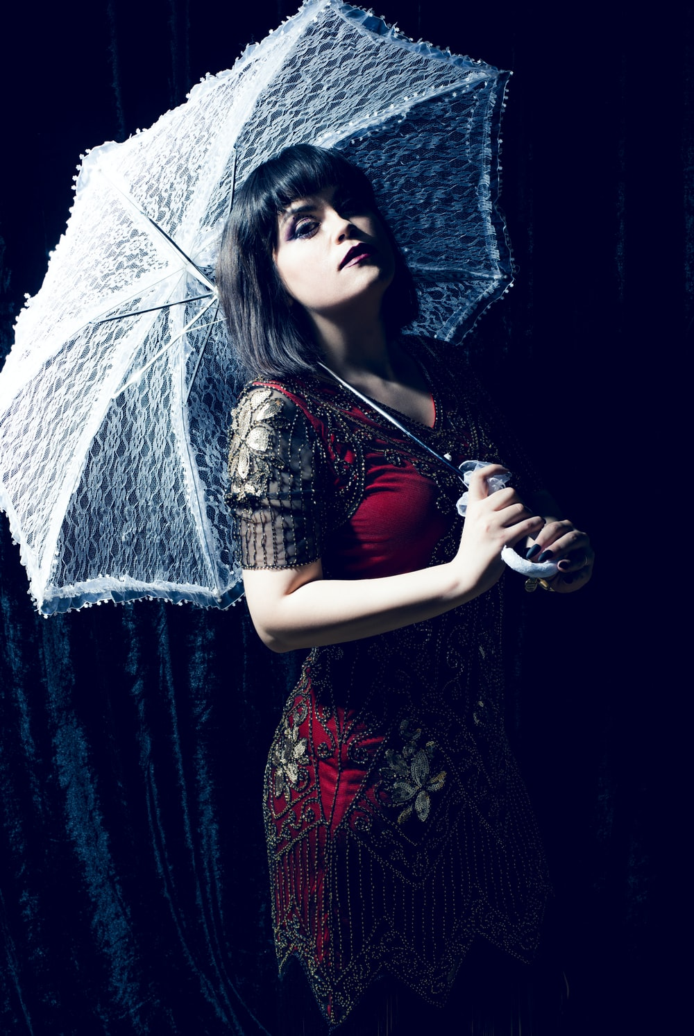 woman in red and black dress holding umbrella