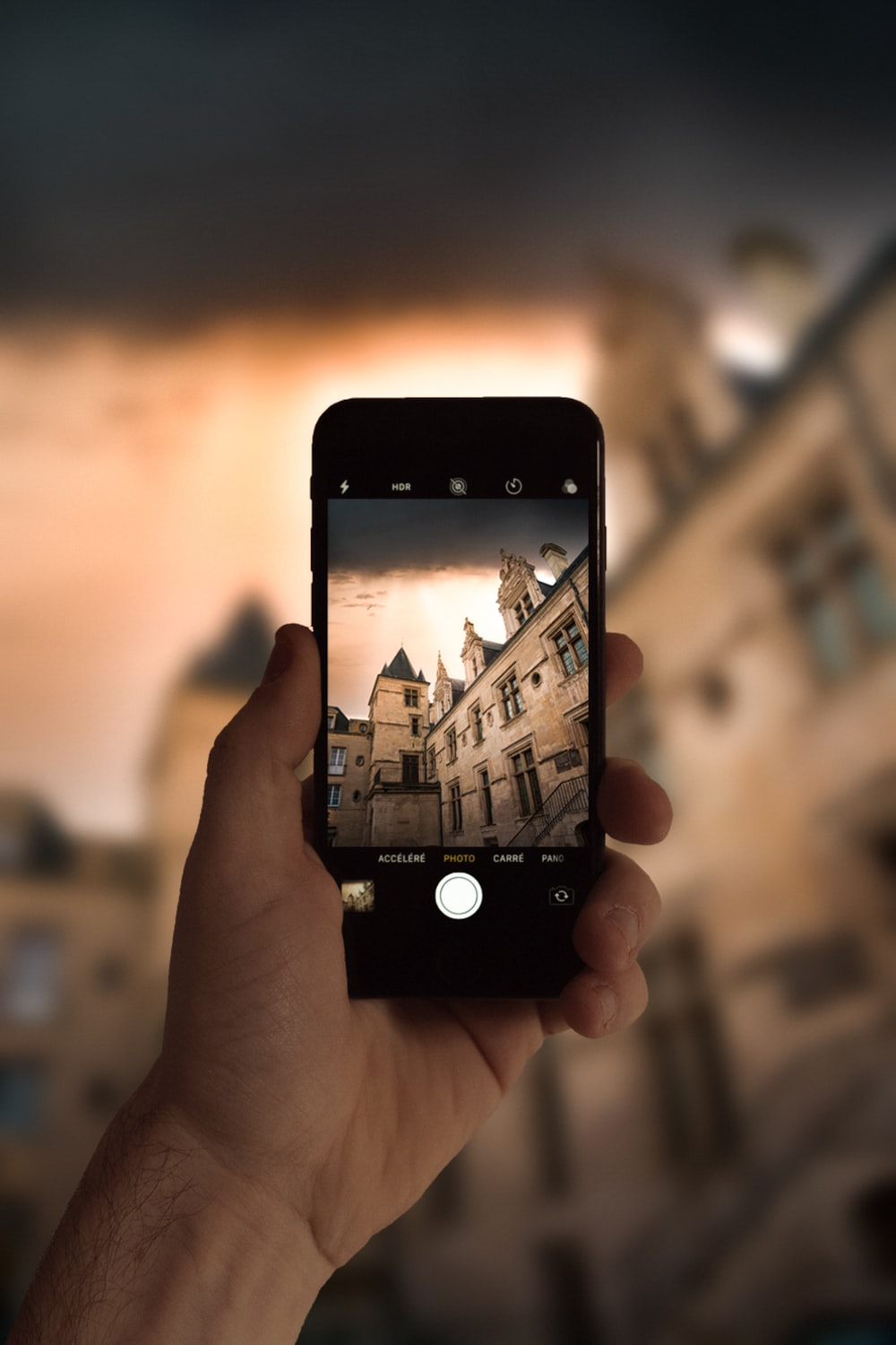 person holding black iphone 4 taking photo of city buildings during daytime