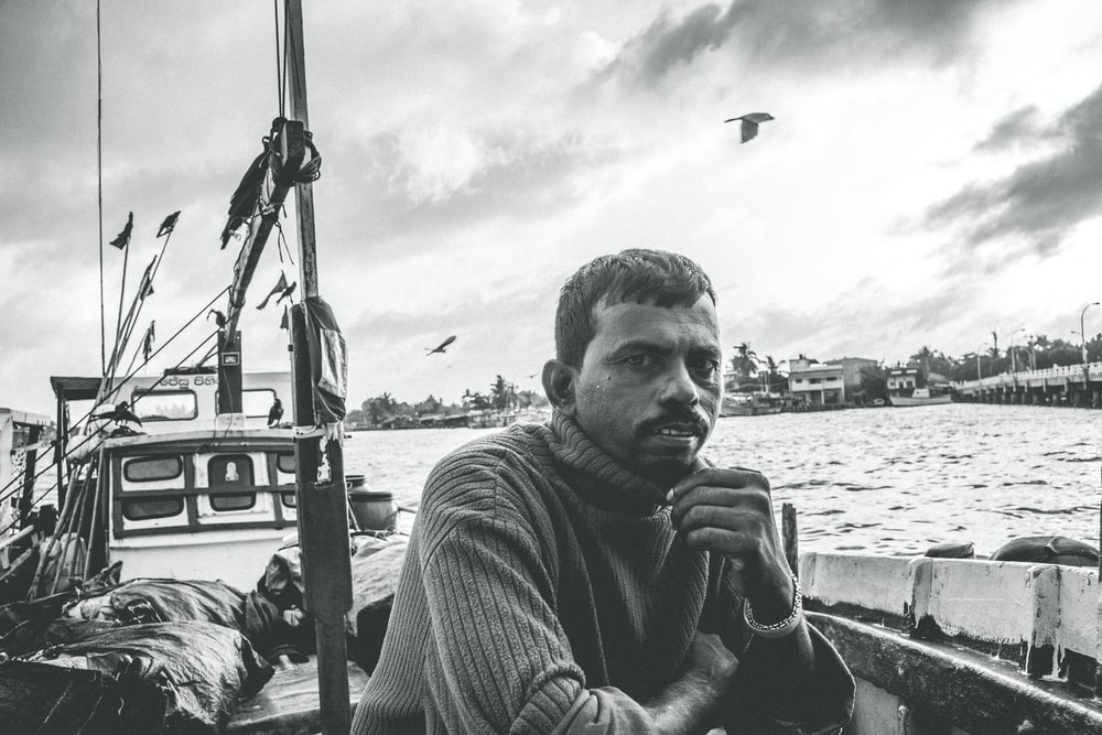 grayscale photo of man in striped shirt sitting on boat