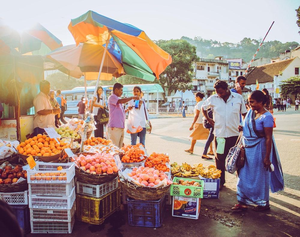 people walking on street with fruit display during daytime