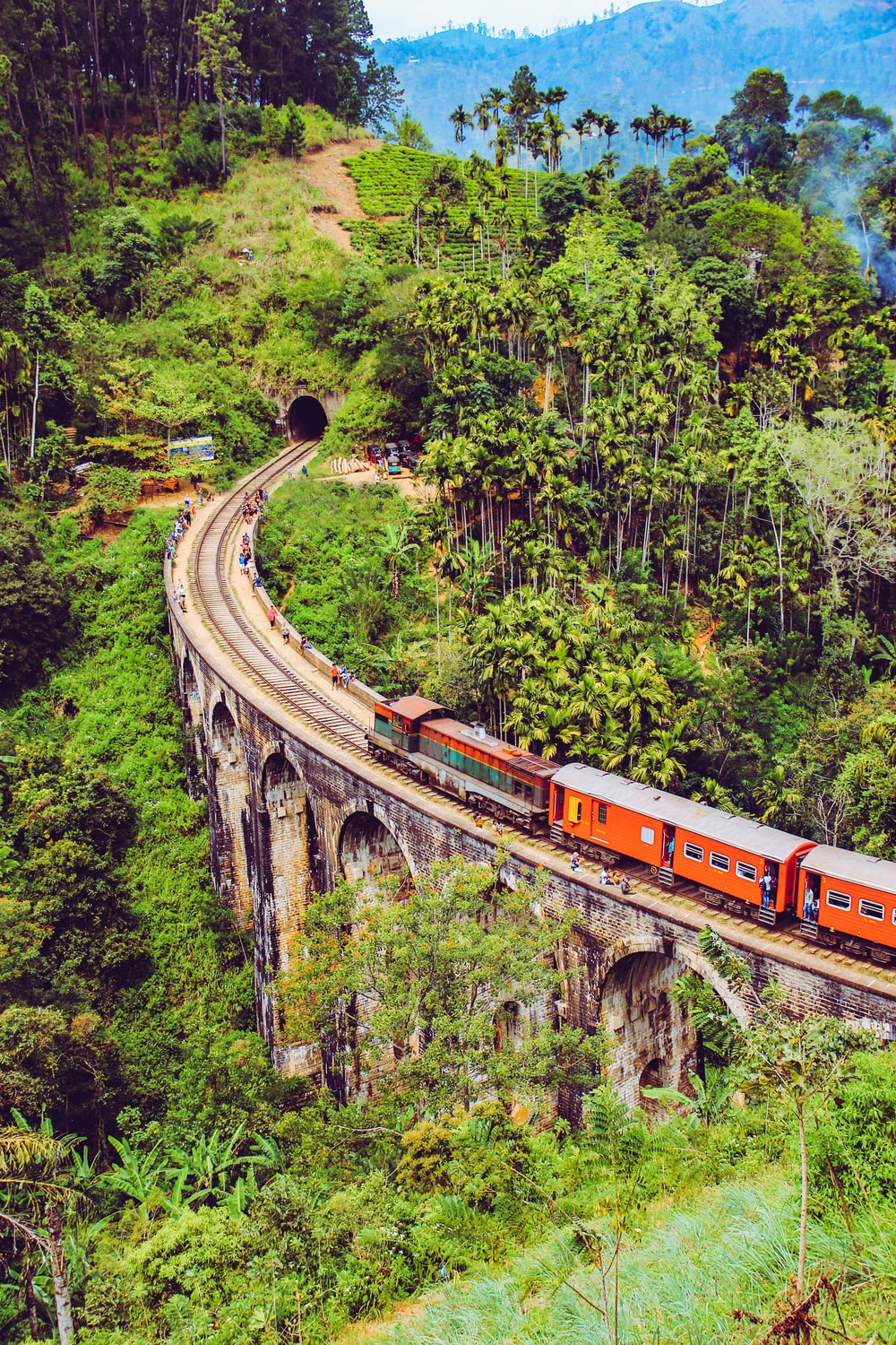 Red And White Train On Rail Track Surrounded By Green Trees During Daytime Photo Free Nine Arch Bridge Image On Unsplash Nature railway rails stone arch trees