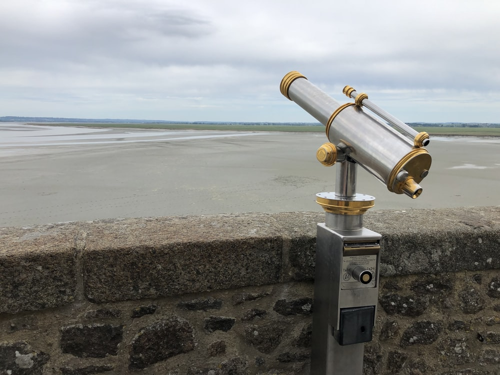 stainless steel telescope on gray concrete wall near sea during daytime