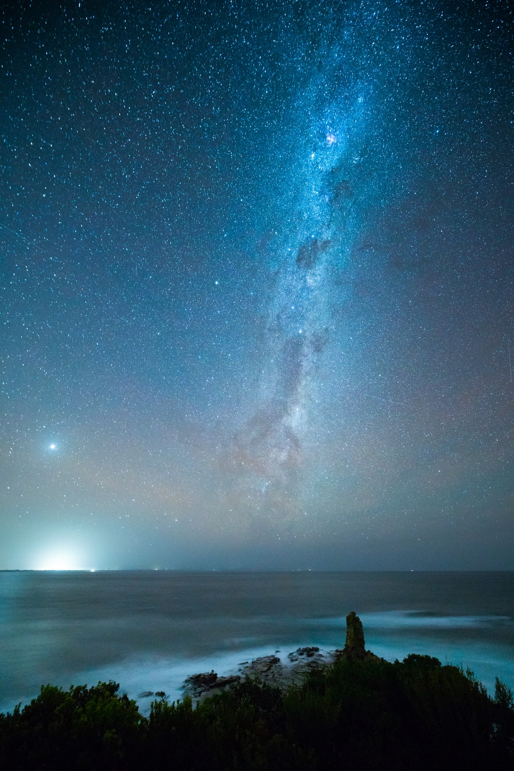 person standing on beach under starry night