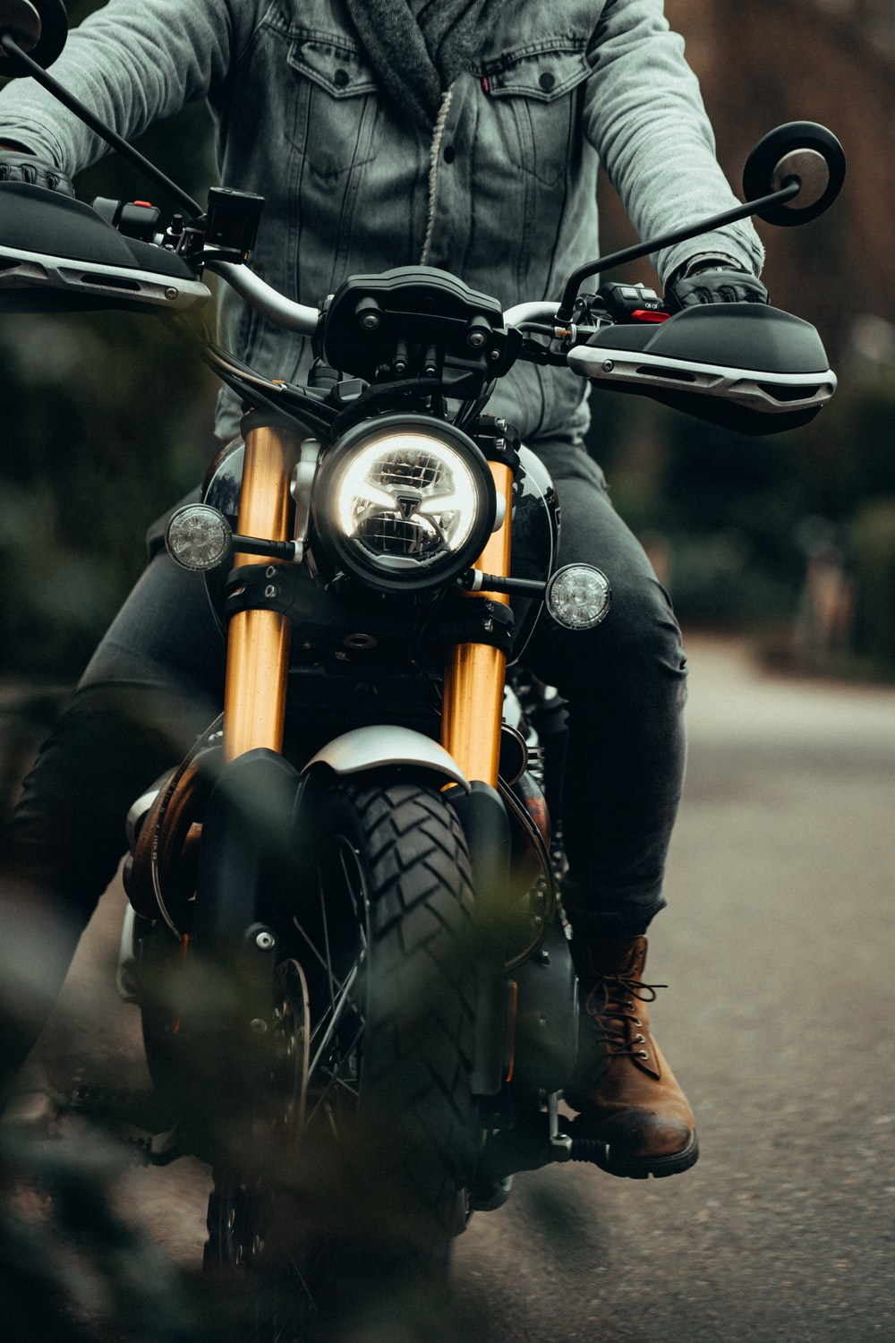 person in black leather jacket riding on black motorcycle