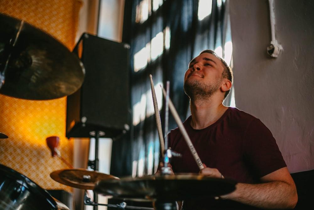 man in red crew neck shirt playing drum