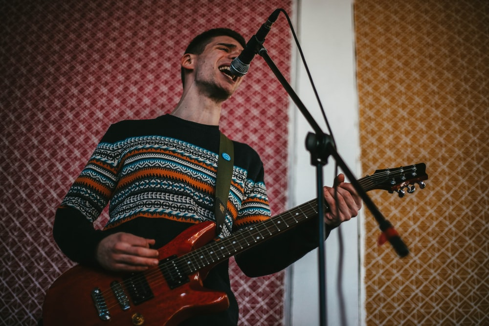 man in red white and blue striped shirt playing electric guitar