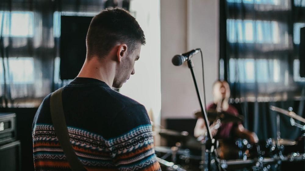 man in black crew neck shirt singing