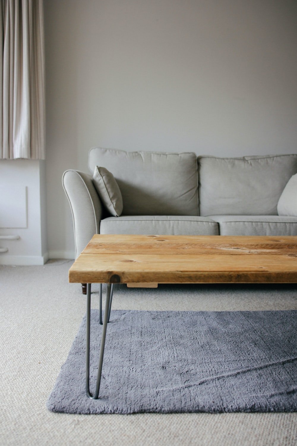 brown wooden table beside white couch