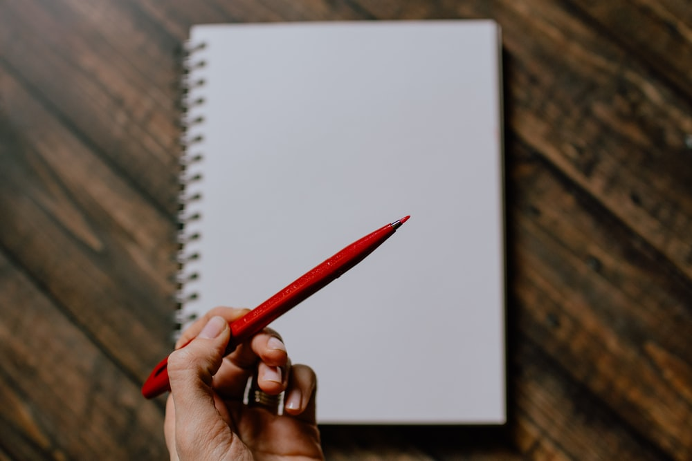 person holding red pencil writing on white paper