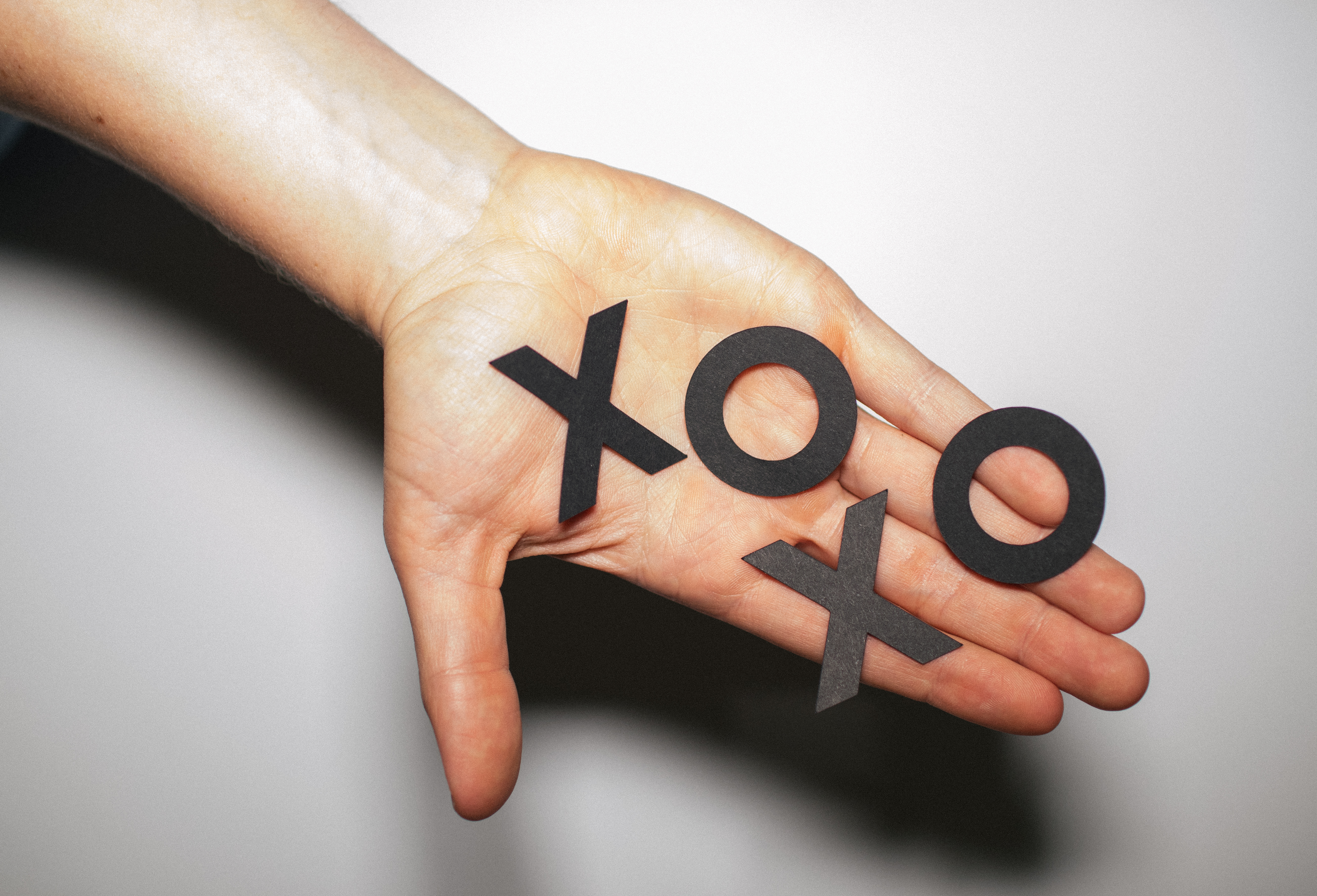 Hand holding X's and O's