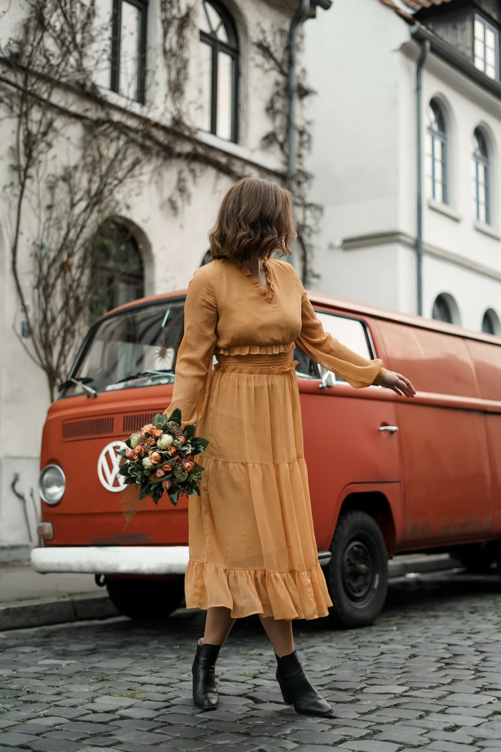 woman in yellow long sleeve dress leaning on red car during daytime
