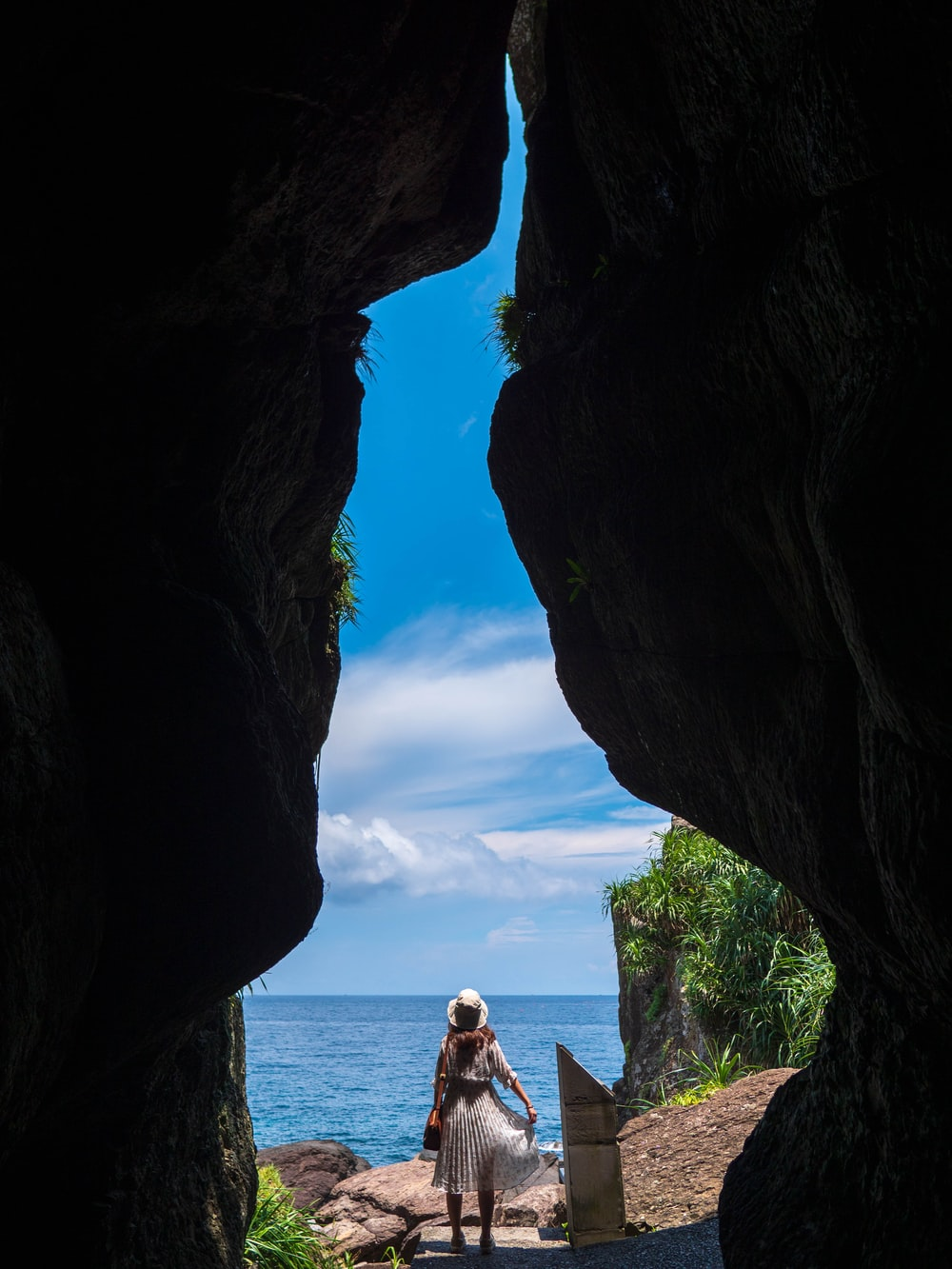 woman in white shirt sitting on rock formation during daytime