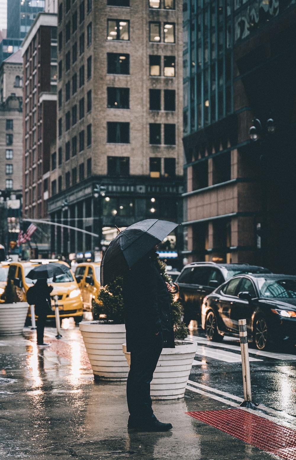 person in black coat holding umbrella walking on pedestrian lane during daytime