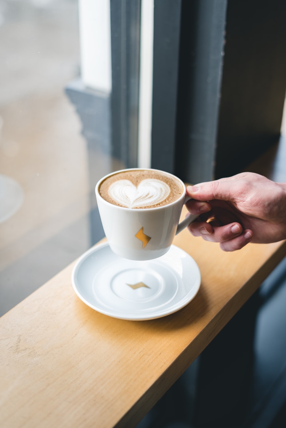 person holding white ceramic cup with saucer