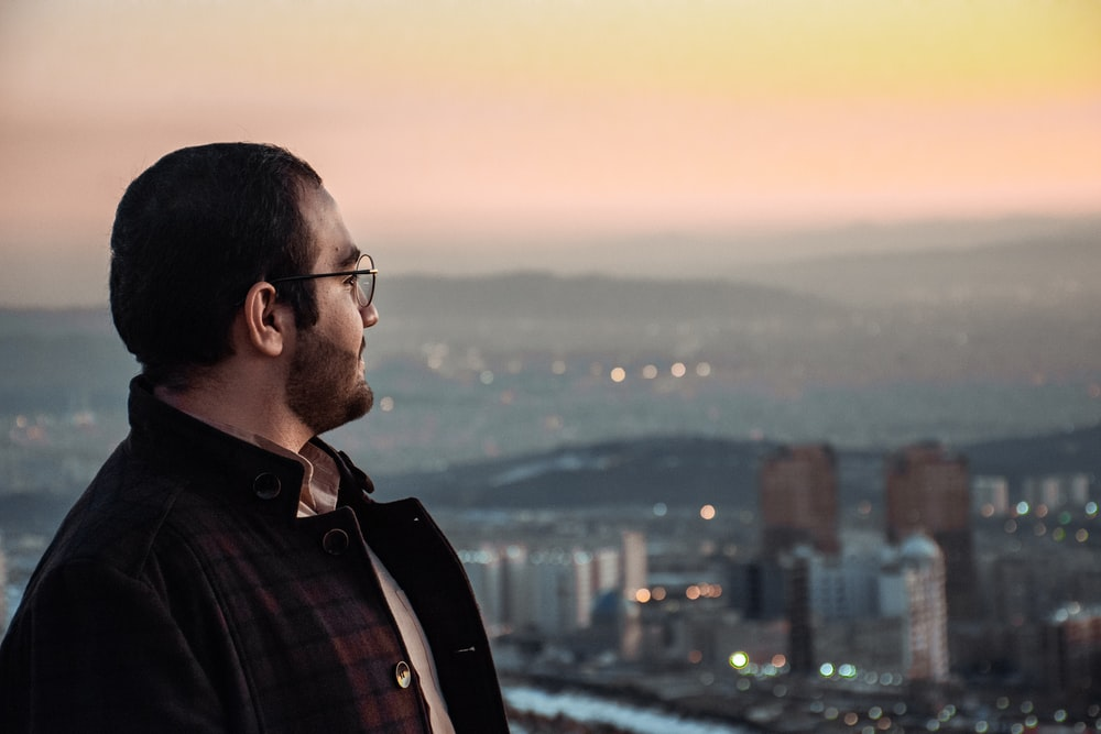 man in black and white plaid button up shirt looking at city buildings during sunset