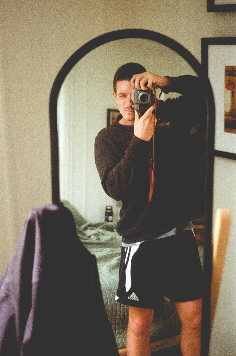 woman in brown jacket taking photo in front of mirror
