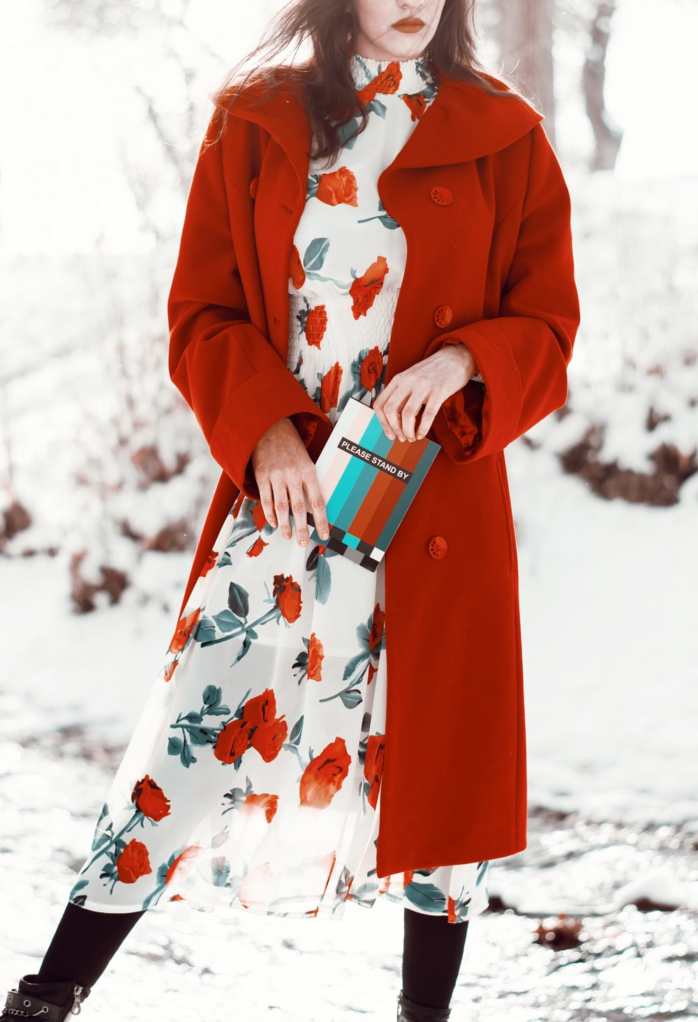 woman in red coat holding white ceramic mug