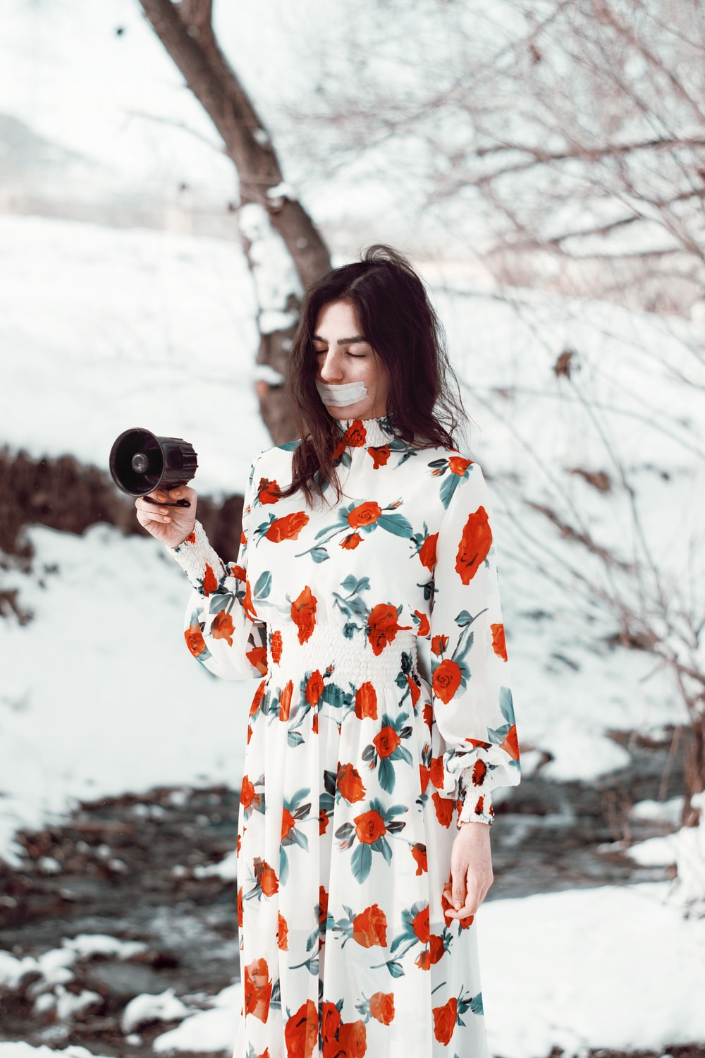 woman in white and red floral dress holding black camera