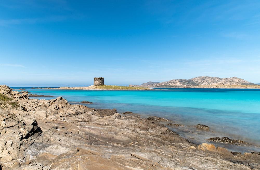 brown rock formation on blue sea under blue sky during daytime