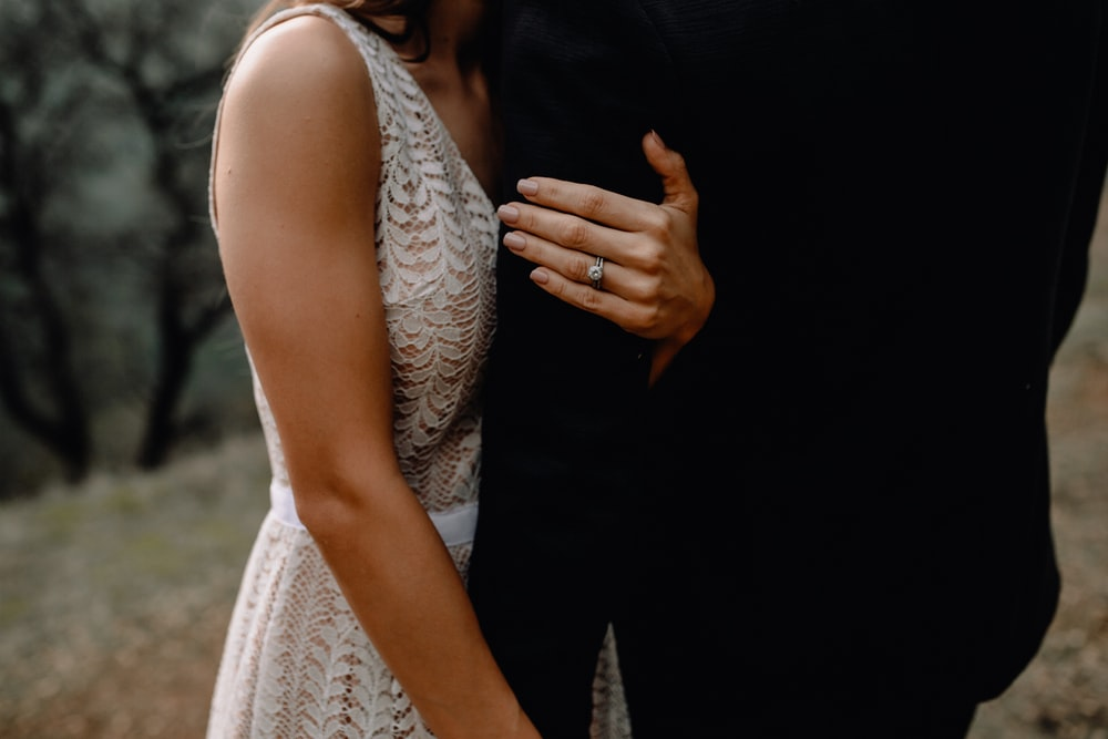 woman in white lace sleeveless dress holding man in black suit