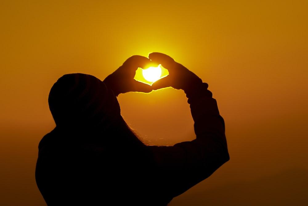 silhouette of man holding sun