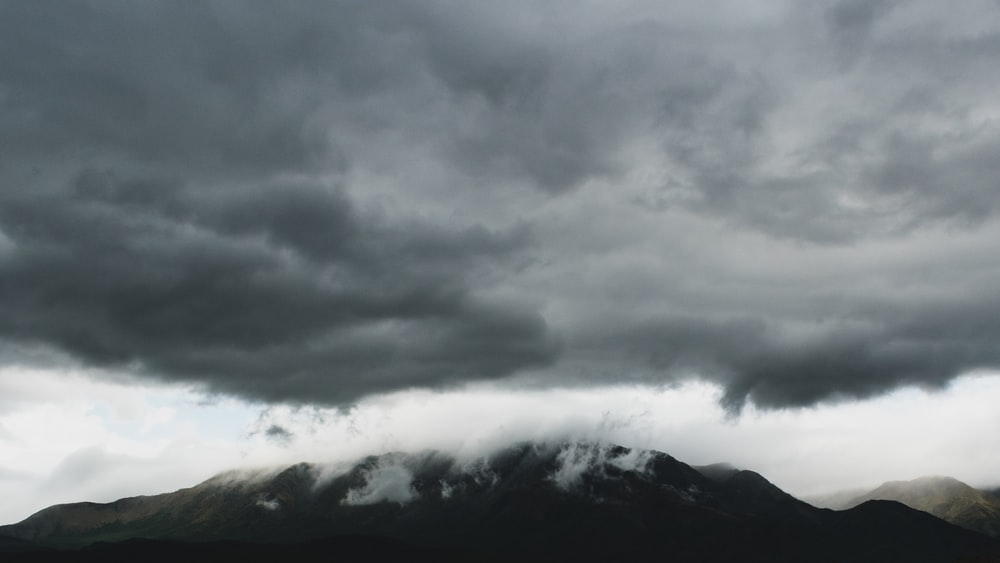 black and white mountain under gray clouds