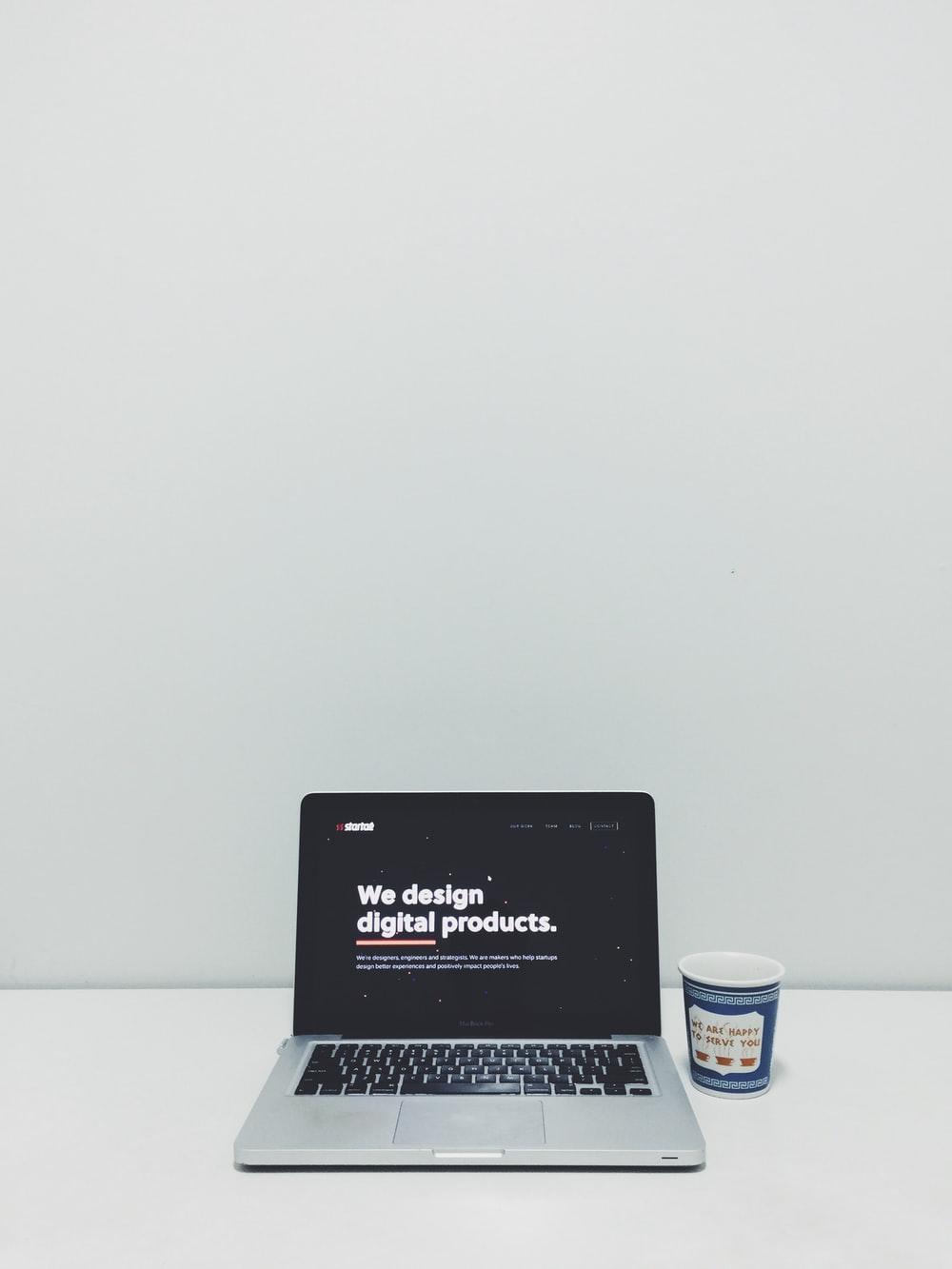 macbook pro beside white and blue plastic cup