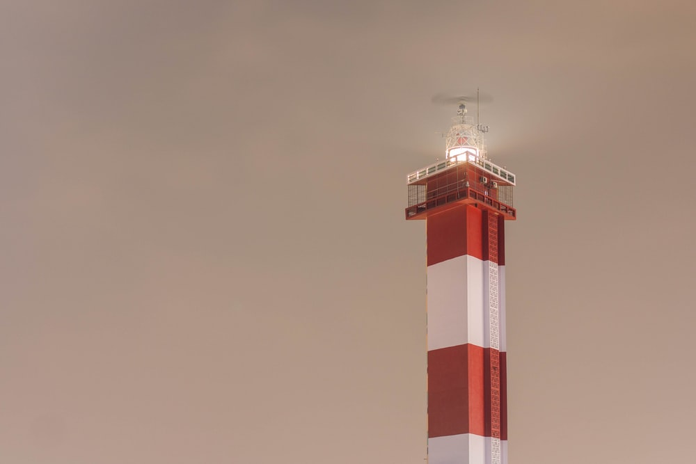 red and white tower under gray sky