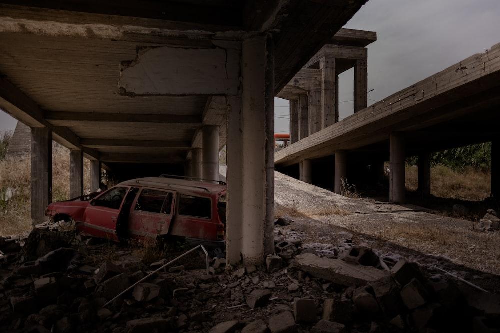 red car under bridge during daytime