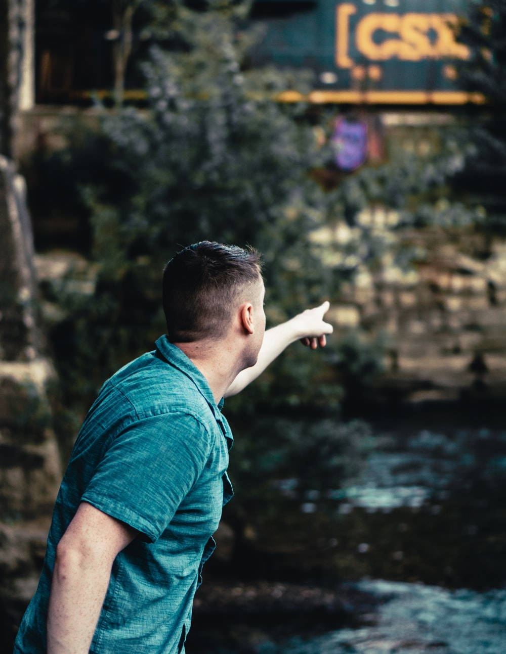 man in blue t-shirt standing near body of water during daytime