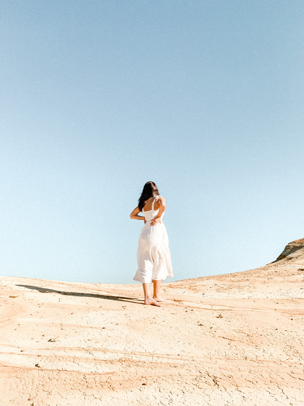 woman in white dress standing on brown sand during daytime