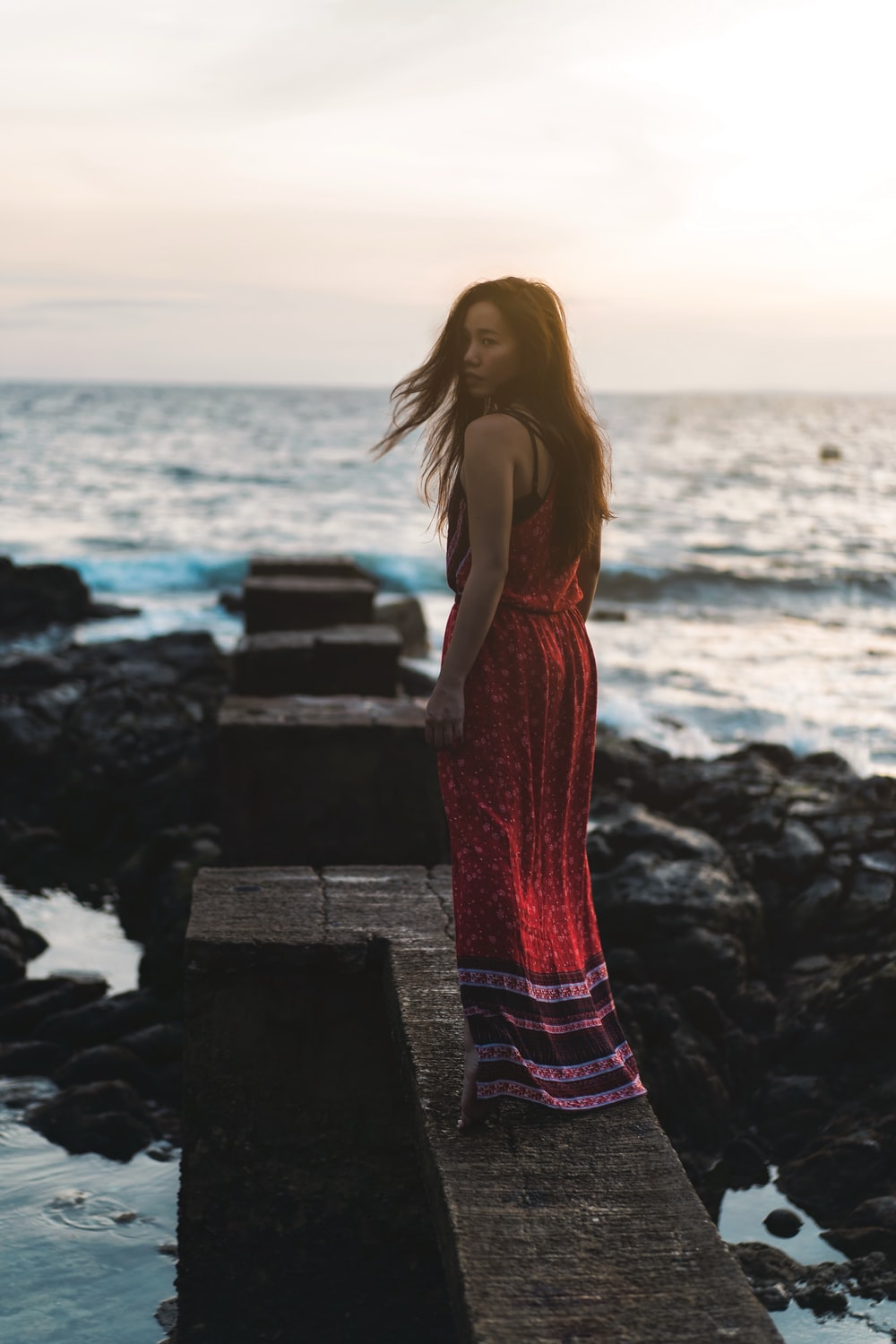 woman in red spaghetti strap dress standing on rock near sea during daytime