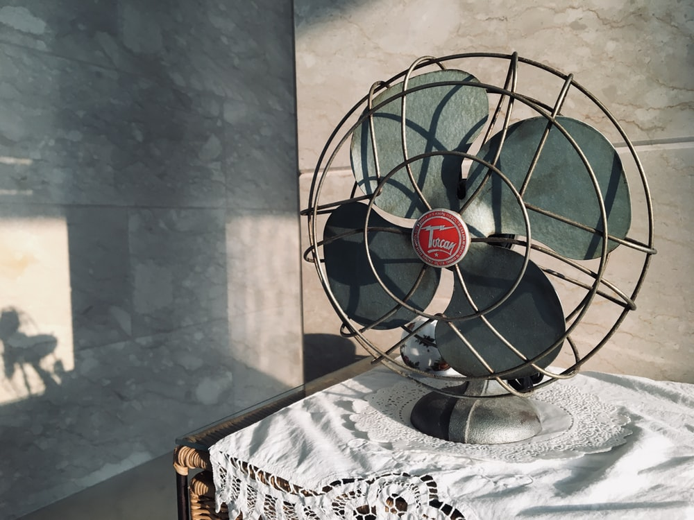 black desk fan on white and black floral table cloth