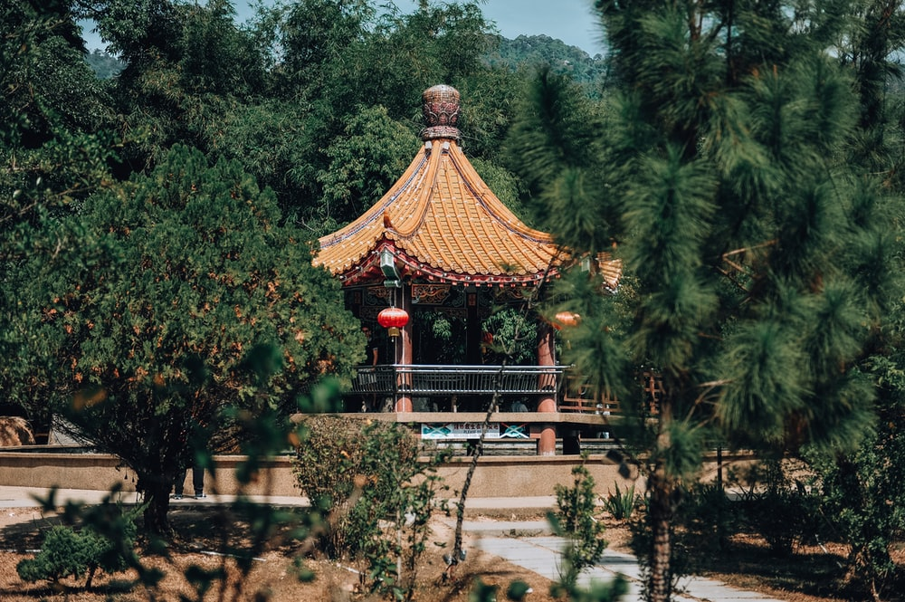 brown and red wooden temple surrounded by green trees during daytime
