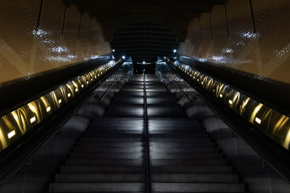 black and brown escalator in tunnel