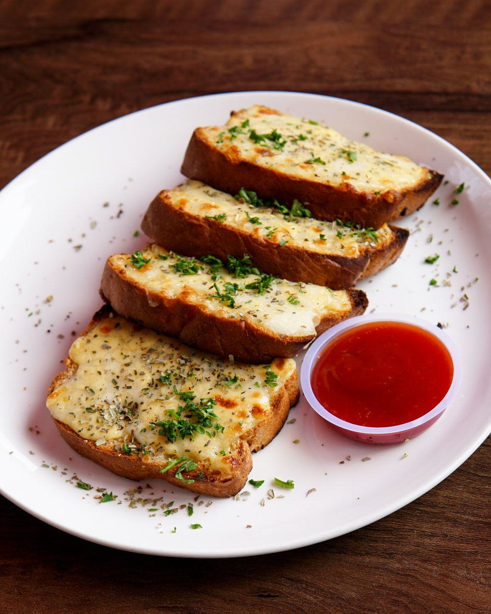toasted bread with tomato sauce on white ceramic plate