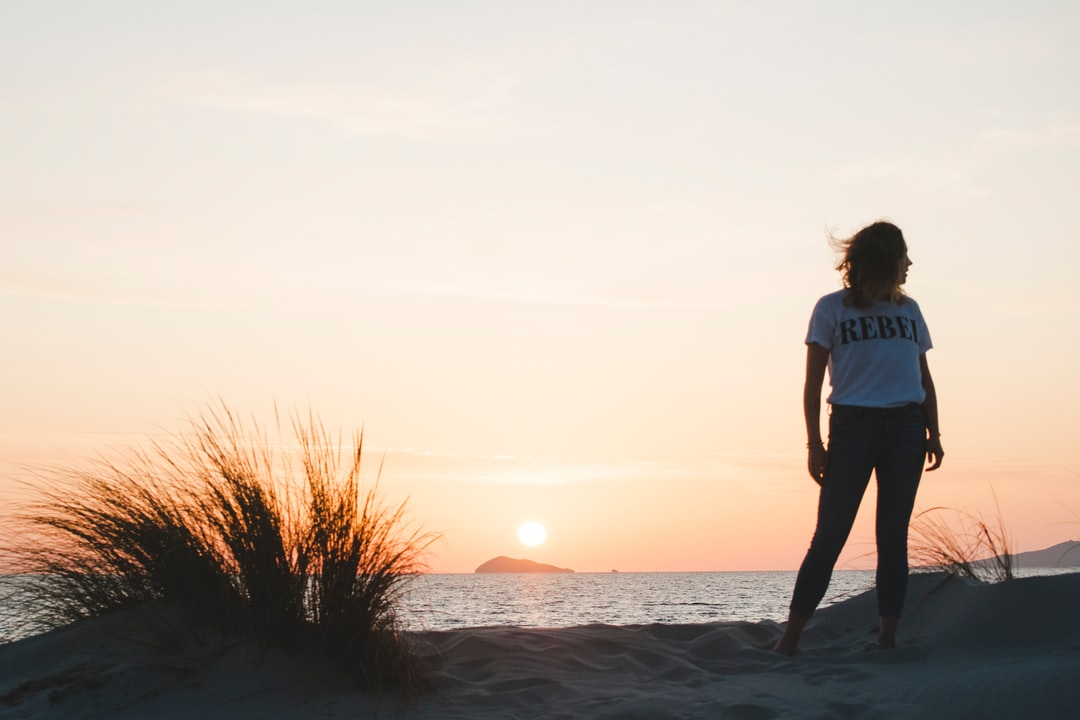 Woman In Blue T-Shirt Standing On Seashore During Sunset - unsplash