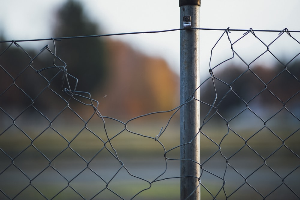 grey metal fence with barbwire