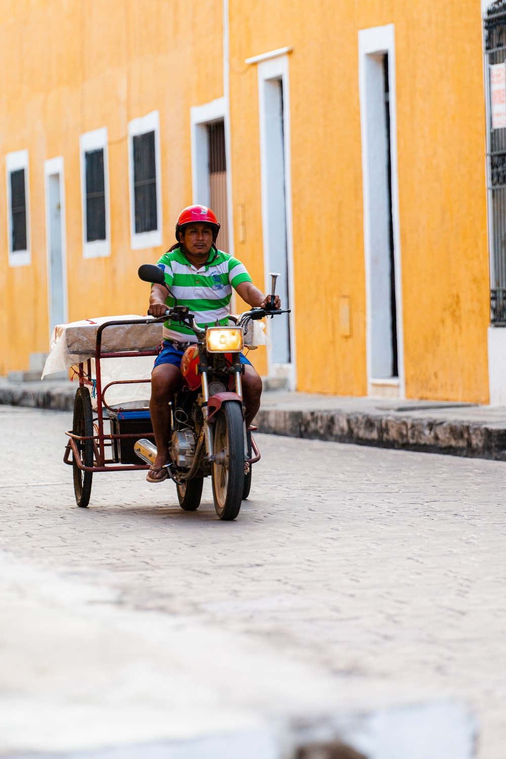 boy in green jacket riding on brown and black trike during daytime
