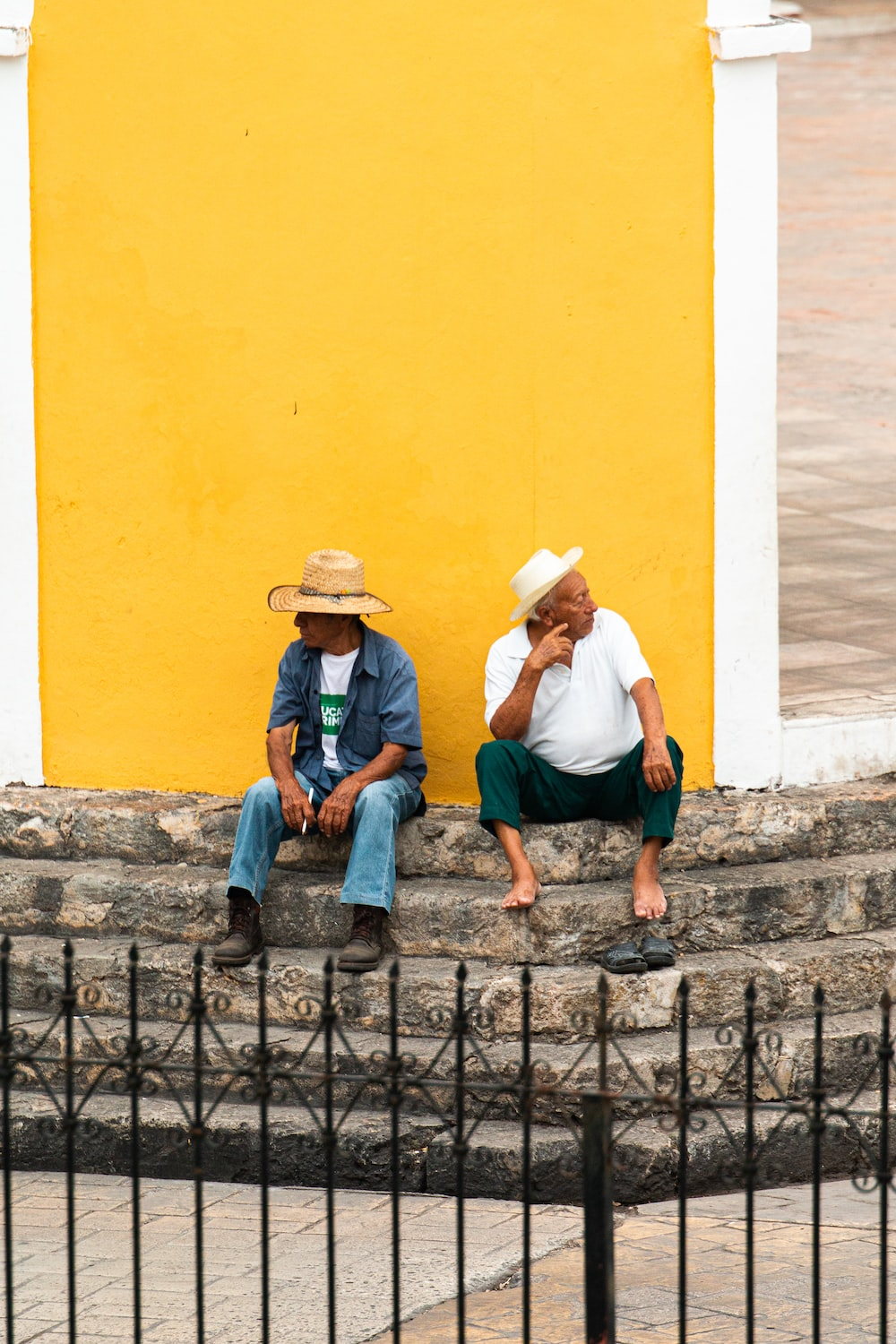 2 men sitting on concrete stairs