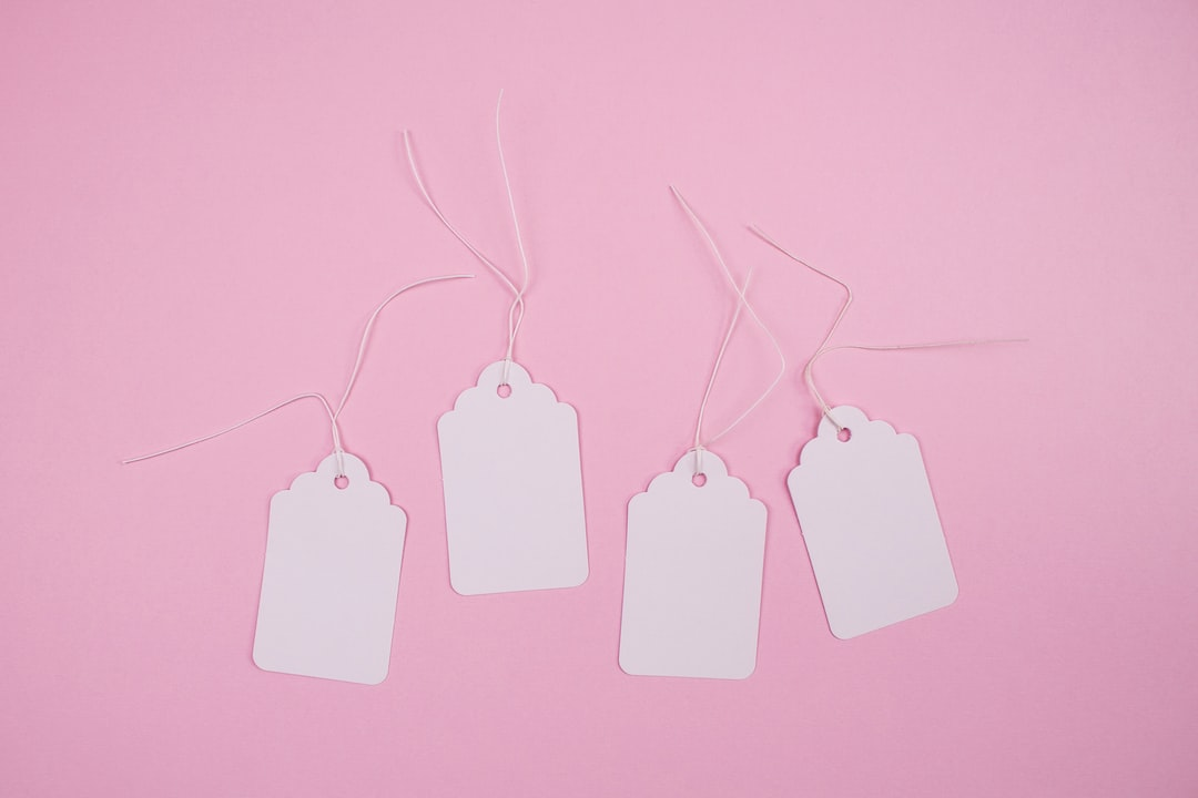 White paper hang tags against pastel pink background with copy space. Ideal for sale promotions and social media