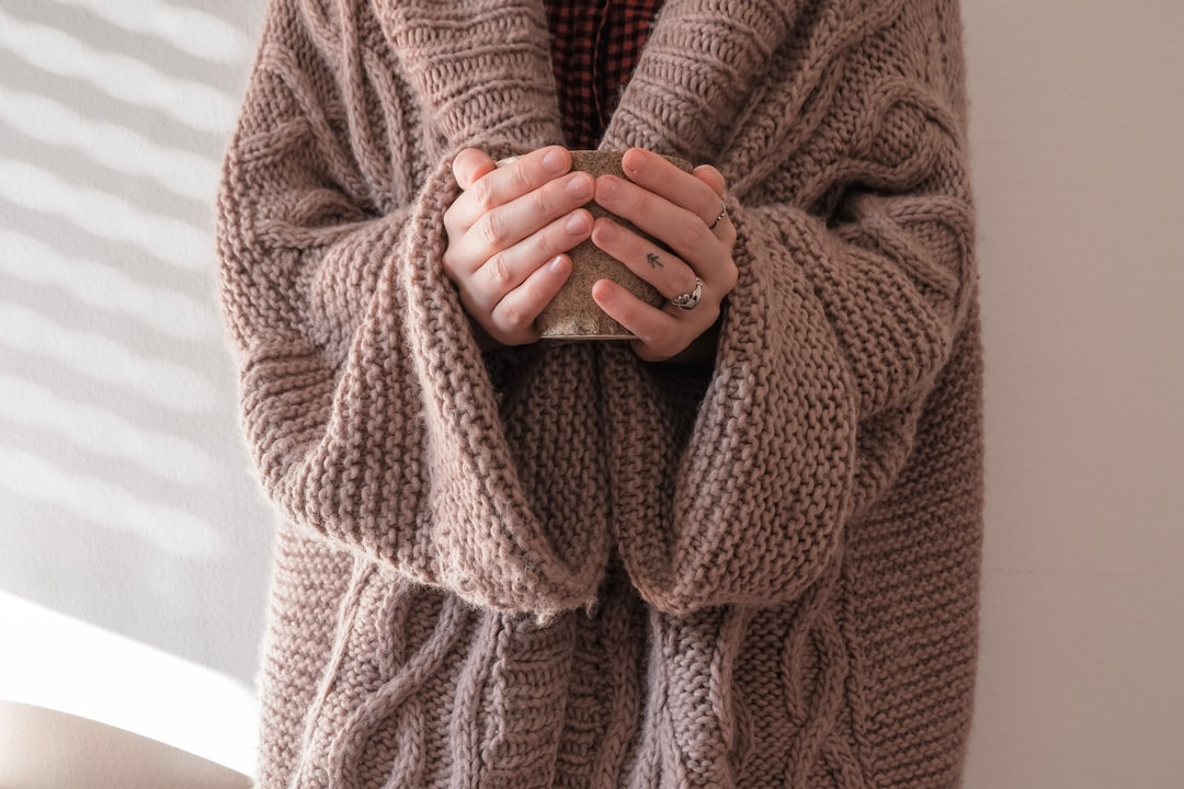 Hygge Hands with a warm cup of coffee and giant sweater.