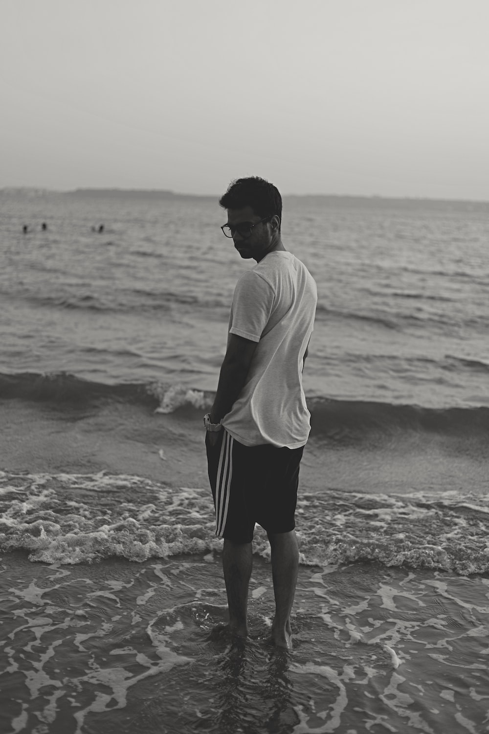man in white shirt and black shorts standing on beach during daytime