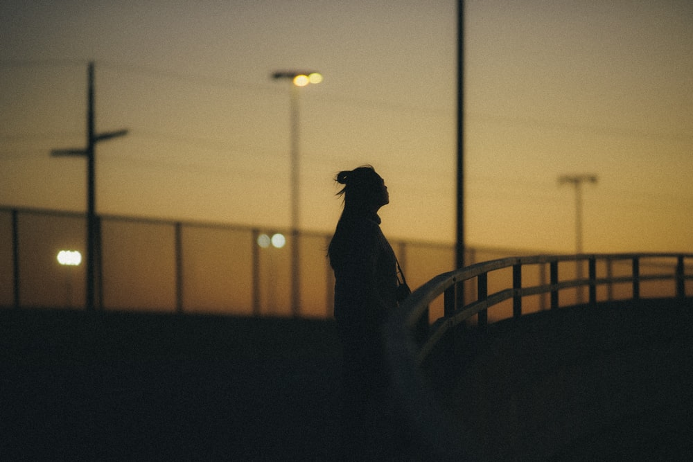 silhouette of person standing on balcony during sunset