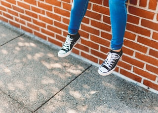 person in blue denim jeans and black and white sneakers