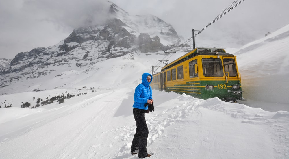 man in blue jacket and black pants standing on snow covered ground near yellow train during